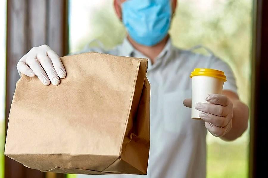 persona entregando comida con protocolos de seguridad