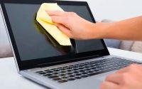 Persona limpiando computadora portátil