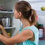chica escogiendo alimentos del refrigerador