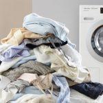 pila de ropa sucia frente a lavadora
